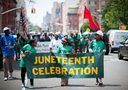 Participants march in the Juneteenth celebration parade through the streets of Harlem in New York