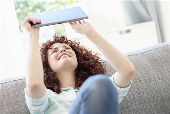 Woman using digital tablet on sofa (Blend Images via AP Images)